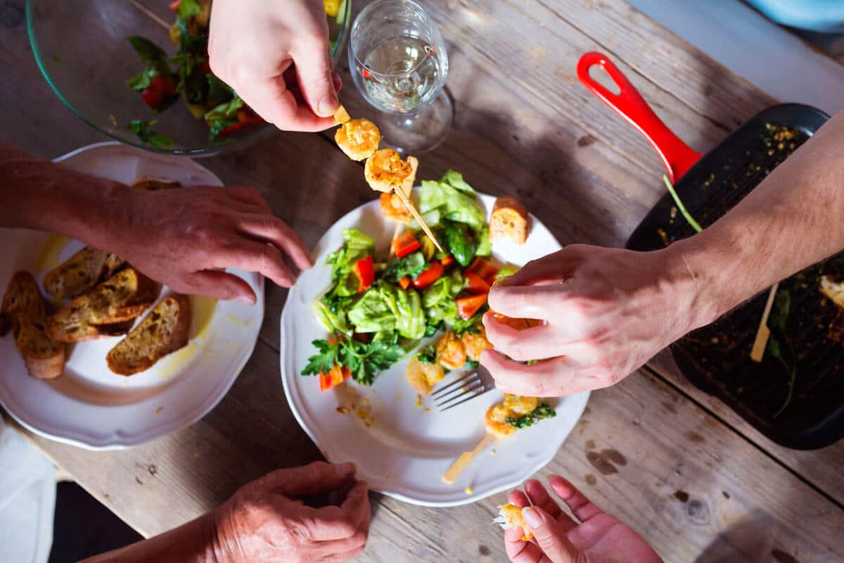 graphicstock-unrecognizable-people-eating-prawns-salad-and-bread-together_r0gjsVjTb- (1)